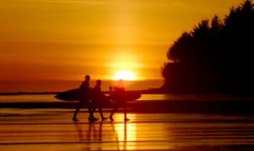 3 surfers walking with surfboards at sunset on a beach in Tofino, BC, Canada.